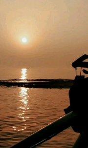 一叶扁舟缓缓摇过朝阳下的光柱,满眼旭日东升,一派生机盎然的模样也很美#去哪儿过年